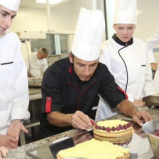 Four student chefs watching a teacher decorate a cake